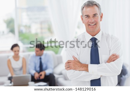 Executive posing while his colleagues are working in cosy meeting room