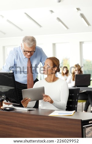 Executive senior business man and businesswoman analyzing data on digital tablet, while sitting at office.  - stock photo