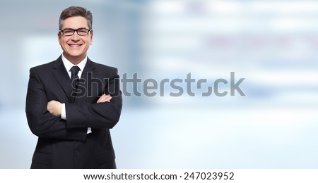 Executive smiling businessman over blue banner background - stock photo