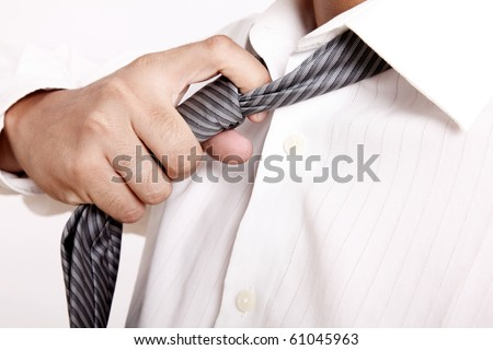 Executive taking off his tie. white shirt