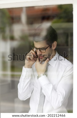 Executive young businessman standing behind window while using his handy. Small Business. - stock photo