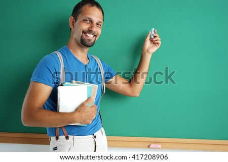 Exemplary student standing near blackboard with books and chalk. Photos adult student,  education concept - stock photo