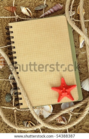 Exercise book and sea stars on sand - stock photo