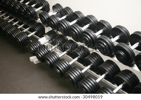 Exercise equipment weights neatly stored in a police gym - stock photo