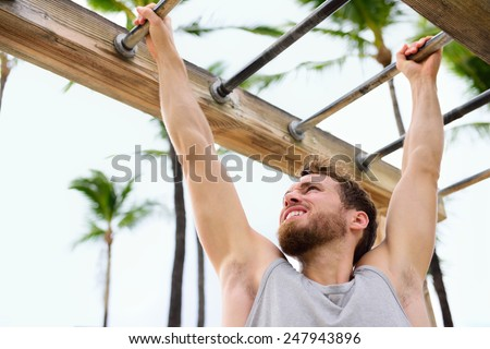 Exercise fitness athlete exercising on monkey bars. Crossfit man working out arms swinging on brachiation ladder as strength training crossfit routine. - stock photo