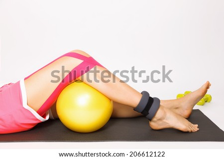 Exercise for injured knee with kinesio tape, ball, ankle weight - stock photo