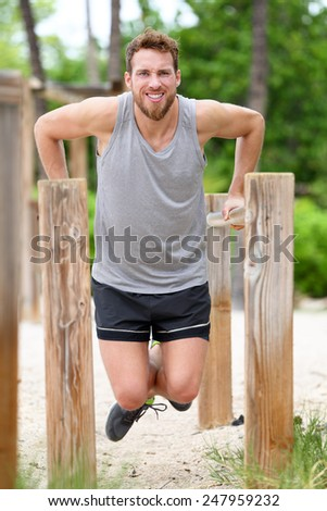 Exercise man workout out arms on dips horizontal bars. Athleter training triceps and biceps doing push ups on fitness station on outdoor gym on beach. - stock photo