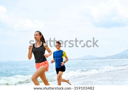 Exercising. Happy Smiling Sporty Runner Couple Running On Beach. Athletic Woman And Fit Man Jogging Near Sea ( Ocean ) During Outdoor Workout. Sports, Fitness. Healthy Lifestyle. Health Concept - stock photo