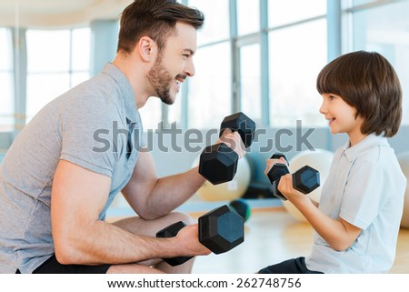 Exercising is fun. Happy father and son exercising with dumbbells and smiling while both standing in health club  - stock photo