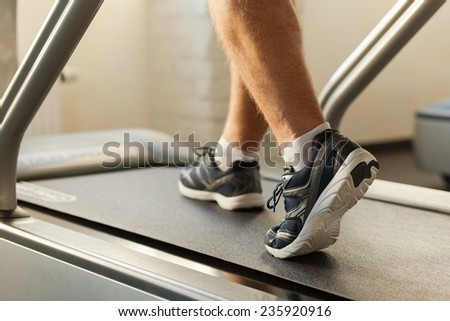 Exercising on treadmill. Close-up of man walking by treadmill in sports club  - stock photo