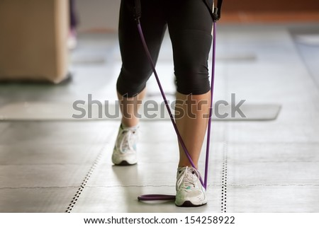 exercising with a resistance band, close up of female legs - stock photo