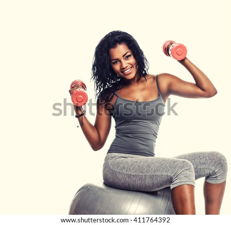 Exercising with fitness ball. Side view of wooman sitting on fitness ball and doing exercises with dumbells. - stock photo