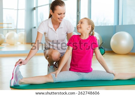 Exercising with instructor. Cheerful instructor helping little girl with stretching exercise in sports club