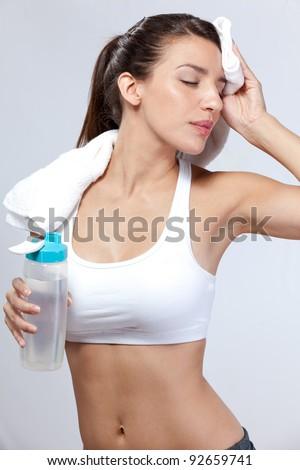 Exercising woman takes break - stock photo