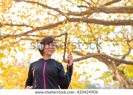 Exercising young Asian woman, listening to music with a smart phone. - stock photo