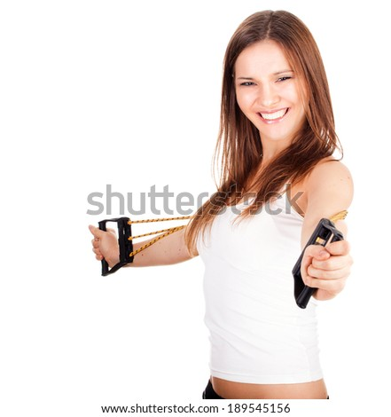 exercising young woman with expander, white background - stock photo