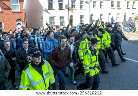 EXETER, ENGLAND - FEBRUARY 21, 2015: Devon and Cornwall Police escort Plymouth football fans  during the police operation at the League 2 football match between Exeter City FC and Plymouth Argyle FC  - stock photo