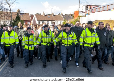 EXETER, ENGLAND - FEBRUARY 21, 2015: Devon & Cornwall Police escort Plymouth Argyle football fans along St James's Road during the League 2 football match between Exeter City FC and Plymouth Argyle FC - stock photo