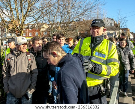 EXETER, ENGLAND - FEBRUARY 21, 2015: Police officer pushes a Plymouth Argyle football fan during the police operation at the League 2 football match between Exeter City FC and Plymouth Argyle FC  - stock photo