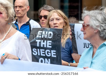 EXETER, ENGLAND - JULY 15, 2014: Peace campaigner hold a sign, which says 'End the Siege on Gaza' during the Peace Vigil for Gaza in Exeter's Princesshay Square. - stock photo