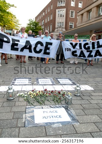 EXETER, ENGLAND - JULY 15, 2014: The peace campaigners hold up peace banners during the Peace Vigil for Gaza in Exeter's Princesshay Square. - stock photo