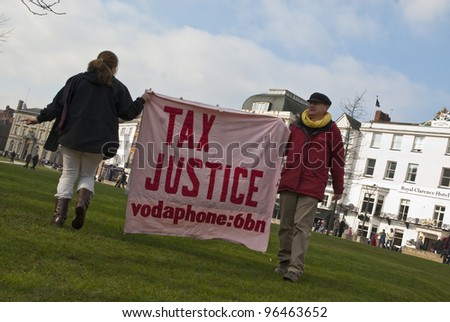 EXETER - FEBRUARY 11: Occupy Exeter activist hold up a Tax Justice banner on Exeter Cathedral green during the Occupy Exeter leaving the Exeter Cathedral Green event in Exeter. - stock photo