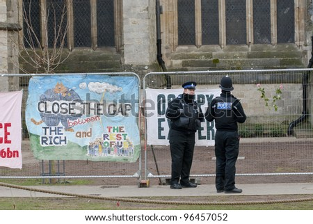"EXETER - FEBRUARY 11: Policemen standing by banner saying ""Close the Gap on the Rich"" and a Occupy Exeter banner on February 11, 2012 in Exeter, UK - stock photo"