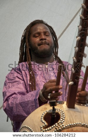 EXETER - JUNE 3: Modou N'Diaye plays the Kora live on the Global Community Stage at the Exeter Respect Festival on June 3, 2012 in Exeter, UK