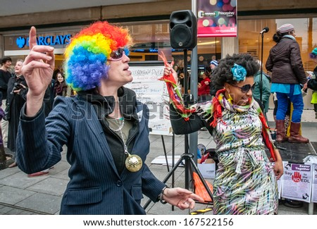 EXETER - NOVEMBER 16: Crystal Carter (left) disco dances with a man in a multicoloured wig during the Exeter Together march and diversity festival on November 16, 2013 in Exeter, Devon, UK  - stock photo