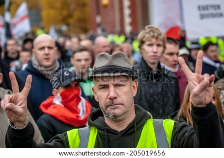 EXETER, UK - NOVEMBER 16: English Defence League member gives a victory sign during the English Defence League march and rally November 16, 2013 in Exeter, Devon, UK - stock photo