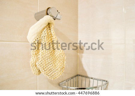 exfoliating glove hanging on shower at the bathroom with copyspace - stock photo