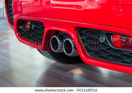 Exhaust pipe of a red car - stock photo