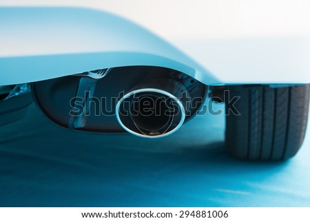 exhaust pipe of a white car on blue carpet - stock photo