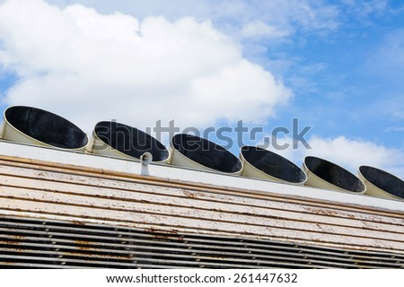 Exhaust vents of industrial air conditioning and ventilation units on the roof top of building and blue sky background. - stock photo