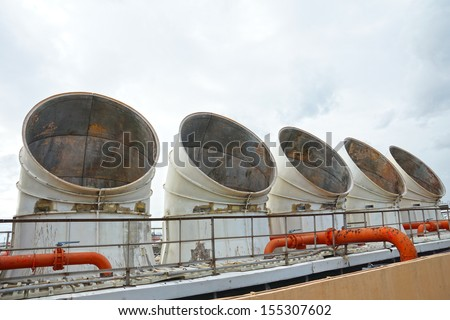 Exhaust vents of industrial air conditioning and ventilation units on the roof top of large building. - stock photo