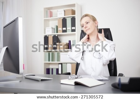 Exhausted Adult Woman Doctor Sitting at her Table While Holding her Nape and Looking at the Computer Screen. - stock photo