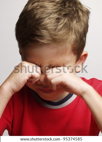 exhausted and sad little kid portrait,rubbing his eyes - stock photo