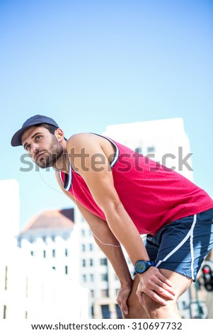 Exhausted athlete leaning forward after an effort on a sunny day