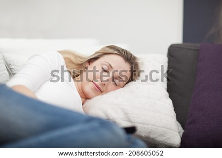 Exhausted attractive young woman taking a nap on the sofa lying curled up with her eyes closed and a lovely smile as she dreams pleasant dreams