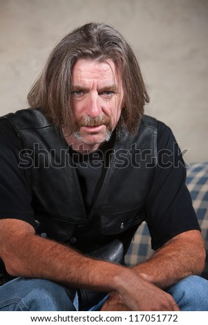 Exhausted biker gang man sitting down indoors