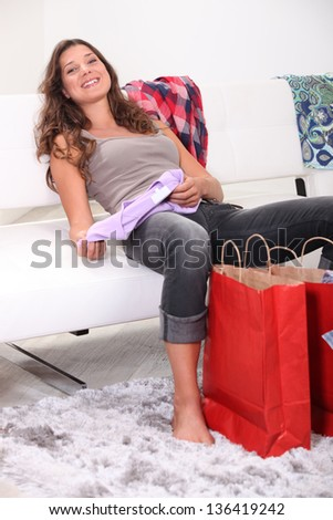 Exhausted brunette sat on couch with her purchases - stock photo