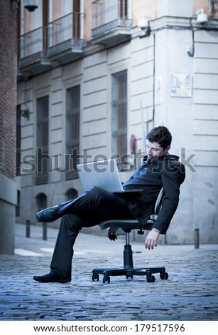 Exhausted Business Man sitting on Office Chair on Street sleeping
