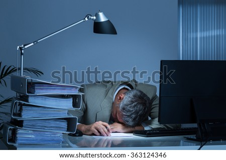 Exhausted businessman leaning head on desk by binders while working late in office - stock photo