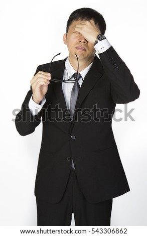 Exhausted Businessman rubbing his eyes with eye glasses take off