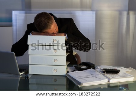 Exhausted businessman sleeping an a stack of files as he works late at the office during the evening as he tries to meet a deadline for the morning - stock photo