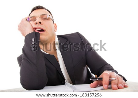 exhausted businessman sleeping at his desk yawning with pencil in hand - stock photo
