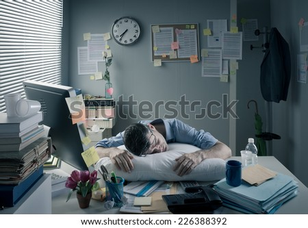 Exhausted businessman sleeping at workplace with a pillow on his desk. - stock photo