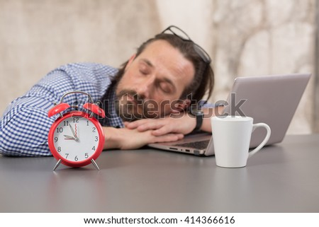 Exhausted businessman sleeping near laptop computer while alrm-clock standing near him. Handsome man resting after hard working day. - stock photo
