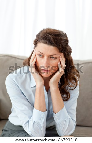 Exhausted businesswoman sitting on her sofa at home - stock photo