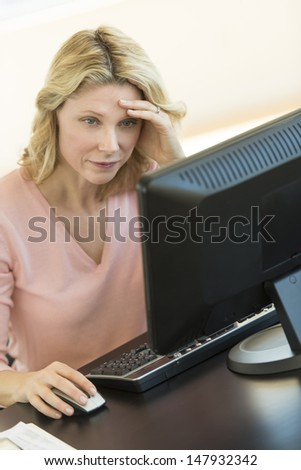 Exhausted businesswoman with head in hands using computer at office desk - stock photo
